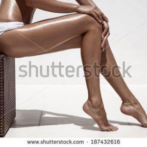 stock-photo-beautiful-woman-tan-legs-against-white-wall-187432616