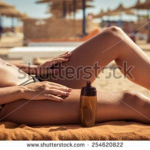 stock-photo-sensuous-slim-woman-applying-suntan-lotion-oil-to-her-body-at-the-beach-254620822